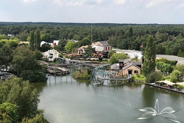 Een prachtig panoramische uitzicht op een achtbaan en de boomstammen