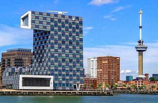 Links het moderne blauwkleurige pand van het onderwijs- en kennisinstelling voor scheepvaart, transport en havenindustrie en rechts de hoge Uitkijktoren Euromast